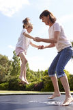 Mother And Daughter Bouncing On Trampoline Together Royalty Free Stock Photo