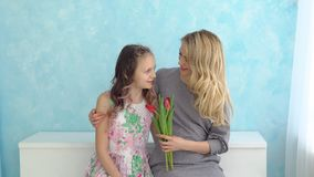 Mother and daughter with a bouquet of tulips sitting on a blue wall background.  stock video