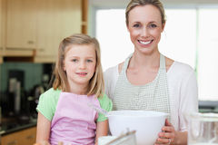 Mother and daughter with bowl in the kitchen Stock Photography
