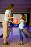 Mother and daughter in a bowling alley, holding a red bowling ball Royalty Free Stock Photos