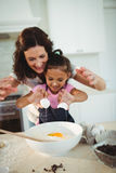 Mother and daughter breaking egg in bowl while preparing cookie Royalty Free Stock Image