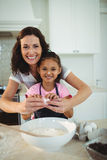 Mother and daughter breaking egg in bowl while preparing cookie Stock Photos
