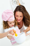 Mother and daughter breaking eggs while cooking Royalty Free Stock Images