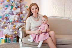 Mother and daughter in bright clothing against a white Christmas Royalty Free Stock Photo