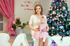 Mother and daughter in bright clothing sitting on a background o Royalty Free Stock Photography
