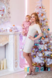 Mother and daughter in bright clothing standing against a white Royalty Free Stock Image