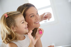 Mother and daughter brushing her teeth Stock Photo