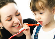 Mother and daughter brushing teeth stock photo