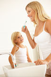 Mother And Daughter Brushing Teeth In Bathroom Royalty Free Stock Photo