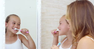 Mother and daughter brushing teeth stock video footage