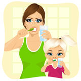 Mother and daughter brushing teeth Stock Photos