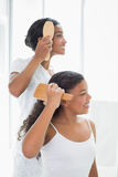 Mother and daughter brushing their hair together Stock Images