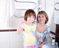 Mother and daughter brushing their teeth Stock Photos