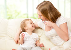 Mother and daughter brushing their teeth stock images