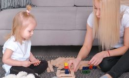 Mother and daughter build from wooden bricks sitting on the floor by the couch. Mother and daughter build from wooden bricks sitting on the floor by the couch Stock Images