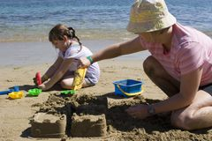 Mother and daughter building a castle. Mother and daughter at the beach building a castle royalty free stock photo