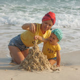 Mother and daughter building sandcastle on the beach Stock Photo