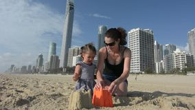 Mother and daughter builds sand castle in Surfers Paradise Australia. Young mother and daughter builds sand castle on Surfers Paradise main beach in Gold Coast stock footage