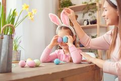 Mother and daughter in bunny ears easter celebration together at home sitting girl covering eyes with eggs stock photo