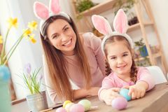 Mother and daughter in bunny ears easter celebration together at home sitting looking camera smiling. Young mother and little daughter wearing bunny ears easter Royalty Free Stock Photo