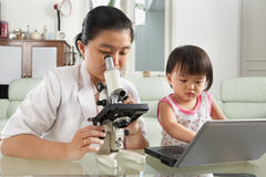 Mother and daughter busy on their own Royalty Free Stock Image
