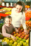 Mother and daughter buying apples Stock Photo