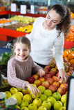 Mother and daughter buying apples Stock Photos