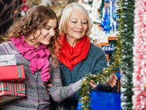 Mother And Daughter Buying Christmas Decorations Royalty Free Stock Photos