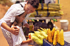 Mother and daughter buying food. On street Royalty Free Stock Photography