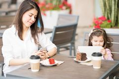 Mother and daughter at cafe using digital devices. Latin women using mobile phone and her daughter using digital tablet while sitting at a restaurant Royalty Free Stock Photography