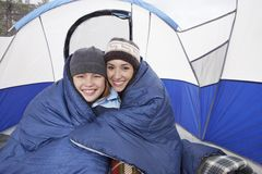 Mother And Daughter Camping In Winter. Portrait of happy mother and daughter wrapped in blanket camping in winter stock photography