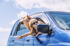 Mother and daughter in the car with sunglasses are traveling rid Stock Images