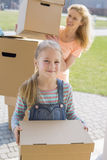 Mother and daughter with cardboard boxes moving into new house Stock Photos
