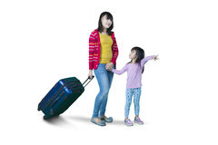 Mother and daughter carrying suitcase on studio Royalty Free Stock Images