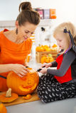 Mother with daughter carving Jack-O-Lantern for Halloween party Royalty Free Stock Images