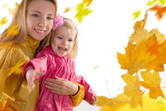 Mother and daughter catching falling leaves Stock Image