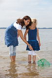 Mother and daughter catching shrimps. Mother and daughter in the sea trying to catch shrimps Royalty Free Stock Images