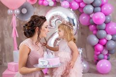 Mother with daughter celebrating family event both dressed in pink airy fancy dresses wearing golden crown on head.Studio shoot of royalty free stock image