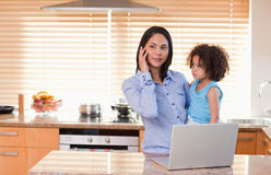 Mother and daughter with cellphone and laptop royalty free stock images