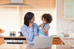 Mother and daughter with cellphone and notebook in the kitchen t Royalty Free Stock Photo