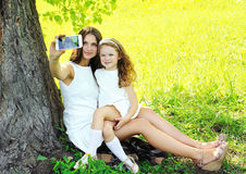 Mother and daughter child taking selfie portrait. On the smartphone outdoors, sunny summer day Royalty Free Stock Image