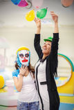 Mother and daughter at a children's party. Sad girl in clown mask and cheerful women at a children's party Royalty Free Stock Image