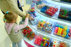 Mother and daughter choose the sweets in sweets shop Stock Photography
