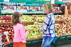 Mother and daughter chooses apples in supermarket Royalty Free Stock Photo