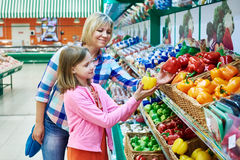 Mother and daughter chooses bell peppers in supermarket Stock Images