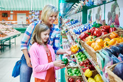 Mother and daughter chooses bell peppers Royalty Free Stock Images