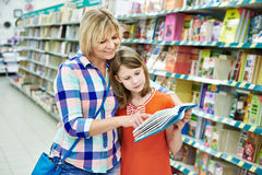 Mother and daughter chooses a book Royalty Free Stock Photography