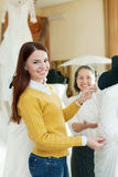 Mother  with daughter chooses bridal gown Stock Photos