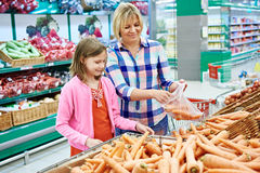 Mother and daughter chooses carrot in supermarket Stock Photos