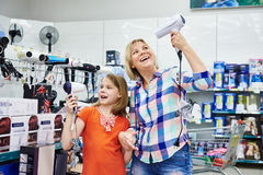 Mother and daughter chooses hairdryer in shop Stock Photography